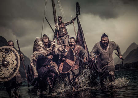 Mad vikings warriors in the attack, running along the shore with Drakkar on the background. 免版税图像