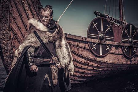 Vikingo guerrero con espada se coloca cerca de Drakkar en la costa.