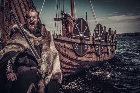 Vikingo guerrero con espada se coloca cerca de Drakkar en la costa. Foto de archivo - 66153154
