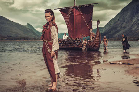 Viking woman standing near Drakkar on seashore. Stock Photo