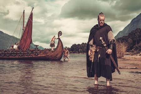 Vikingo guerrero con espada se coloca cerca de Drakkar la orilla del mar.