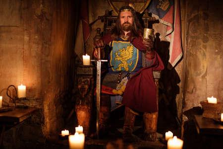 古代の城の奥に玉座に古い中世の王。