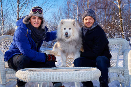 Two friends with dog spend winter holidays together at mountain cottage