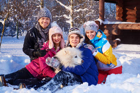 Cheerful friends with dog spend winter holidays together at mountain cottage.