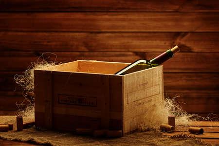 Flasche Wein in der Schachtel im hölzernen Innenraum. Standard-Bild - 102895504