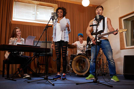 Multiracial music band performing in a recording studio. Фото со стока