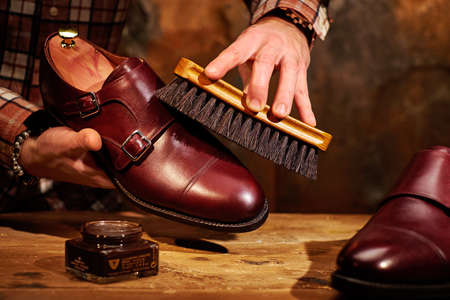 Man polishing leather shoes with brush