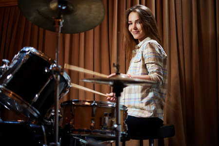 Young cheerful girl behind drums on a rehearsal.