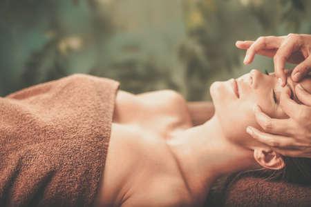 Młoda kobieta o masaż twarzy w salonie spa.