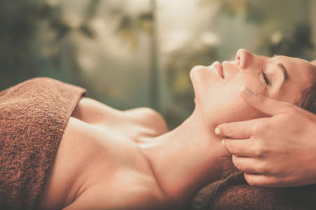 Young woman having face massage in a spa salon. Stock Photo