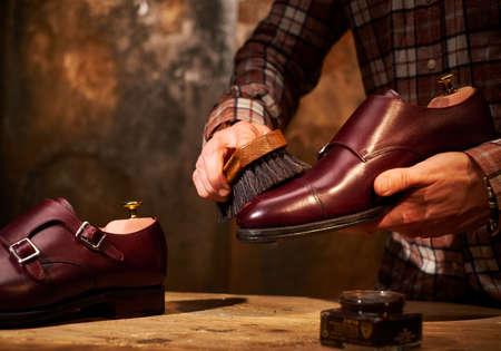Man polishing leather shoes with brush.