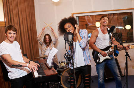 Multiracial music band performing in a recording studio. Reklamní fotografie