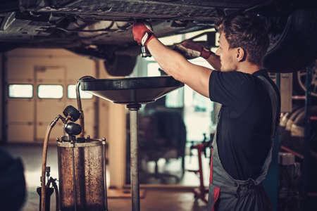 mécanicien automobile Profecional changement d'huile moteur dans le moteur de l'automobile à la station de service de réparation et d'entretien dans un atelier de voiture.