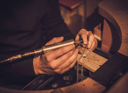 Jeweler at work in jewelery workshop. Banco de Imagens