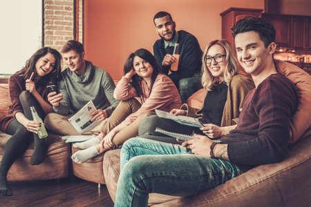 Groep multi etnische jonge studenten die voor examens in huisbinnenland voorbereidingen treffen.