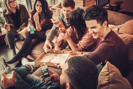 피자 집에서 먹는 멀티 민족 젊은 친구의 그룹