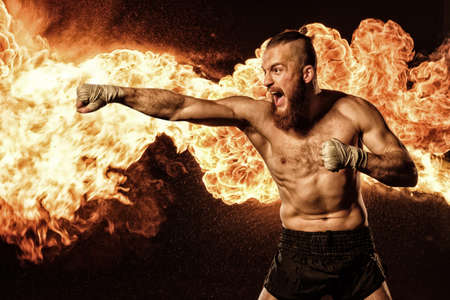Professional fighter shadowboxing with fire and sparks on background Stock Photo