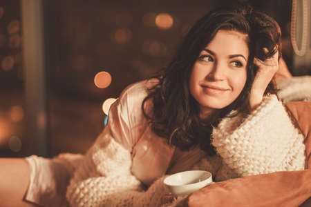 Portrait of beautiful young woman with cup of hot drink in cozy home interior Stok Fotoğraf