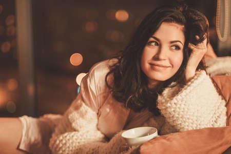 Ritratto di bella giovane donna con tazza di bevanda calda in interni casa accogliente Archivio Fotografico - 69903613
