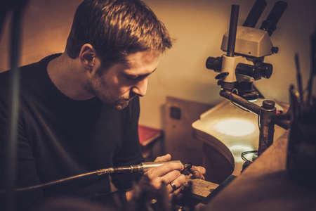 Juwelier bei der Arbeit in der Schmuckwerkstatt Standard-Bild - 68791244
