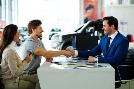 Salesman and customer shaking hands congratulating each other at the dealership showroom. Reklamní fotografie