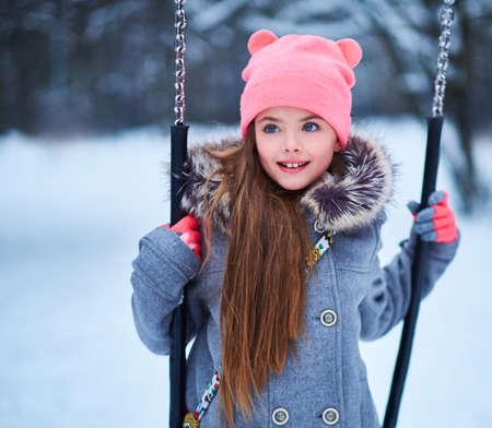 Charmant meisje op schommel in de sneeuwse winter