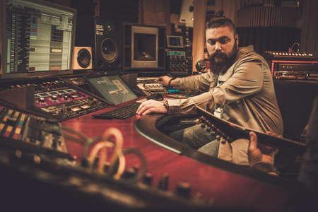 Sound engineer and guitarist recording song in boutique recording studio Foto de archivo