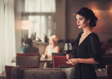 Elegant brunette lady in black evening dress with glass of red w Foto de archivo