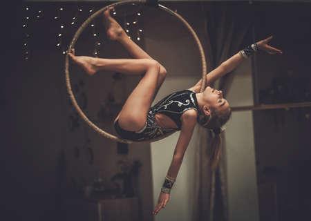 Plastic little girl gymnast on acrobatic ring Standard-Bild