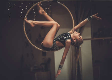 Plastic little girl gymnast on acrobatic ring Archivio Fotografico