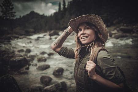 Schöne Frau Wanderer in der Nähe von wilden Gebirgsfluss.