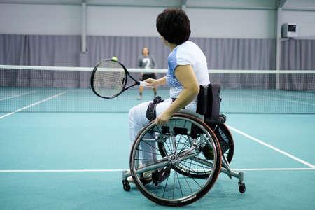 Disabled mature woman on wheelchair playing tennis on tennis court Standard-Bild