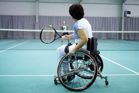 Disabled mature woman on wheelchair playing tennis on tennis court Stockfoto