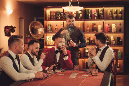 Group of upper class men playing poker in gentlemens club