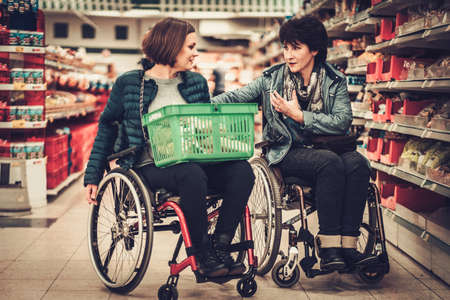Two disabled woman in a wheelchairs in a grocery store Stock Photo