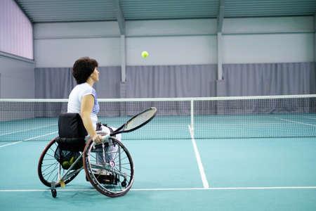 Behinderte reife Frau auf Rollstuhl Tennis spielen auf dem Tennisplatz. Standard-Bild - 72884313