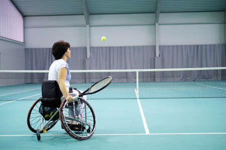 Disabled mature woman on wheelchair playing tennis on tennis court. Archivio Fotografico