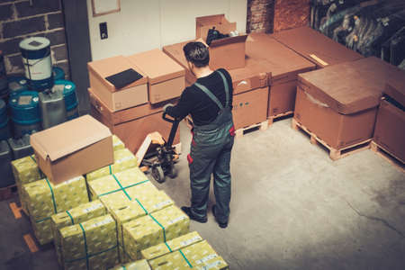 Storekeeper working with pallet truck in a warehouse