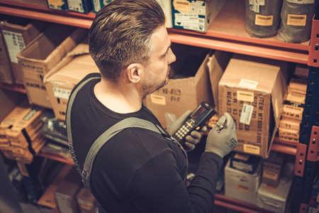 倉庫で働くハンドヘルド バーコード スキャナーと店主
