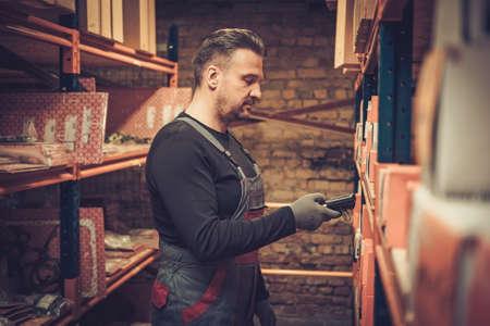 Magazziniere con scanner di codici a barre portatile lavora in un magazzino Archivio Fotografico