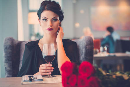 Elegant lady with red roses in restaurant Stock Photo