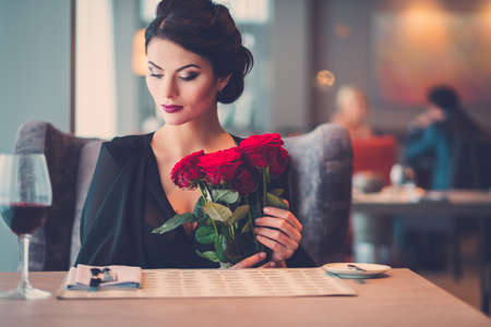 Elegant lady with red roses in restaurant Stockfoto