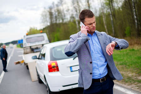 Man belt terwijl de vrachtwagen vraagt om zijn gebroken auto op te halen
