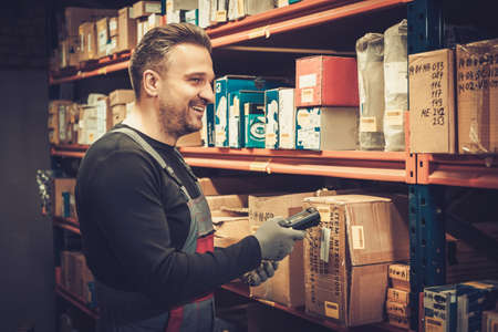 Storekeeper with handheld barcode scanner working in a warehouse