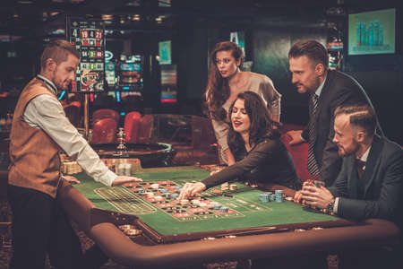 Upper class friends gambling in a casino 版權商用圖片 - 74894998