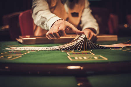 Crupier detrás de la mesa de juego en un casino Foto de archivo - 74894986