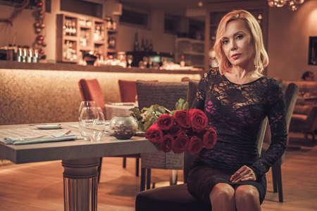 中年のレストランで赤いバラの花束を持つ女性。 写真素材