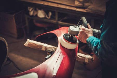 Mechanic polishning car body details in restoration workshop. Banco de Imagens