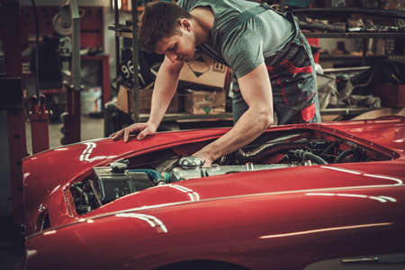 Mechanic working on classic car electrics in restoration workshop.