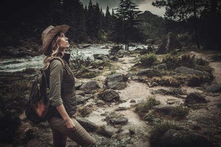 Mooie vrouw wandelaar in de buurt van wilde bergrivier. Stockfoto